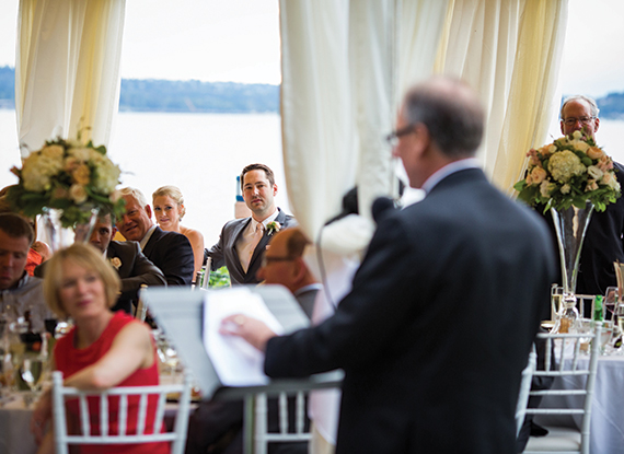 Man Giving Speech At Wedding In Tent On Dock Overlooking Lake Washington At The Woodmark Hotel